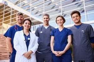 Five healthcare colleagues standing outdoors, group portrait