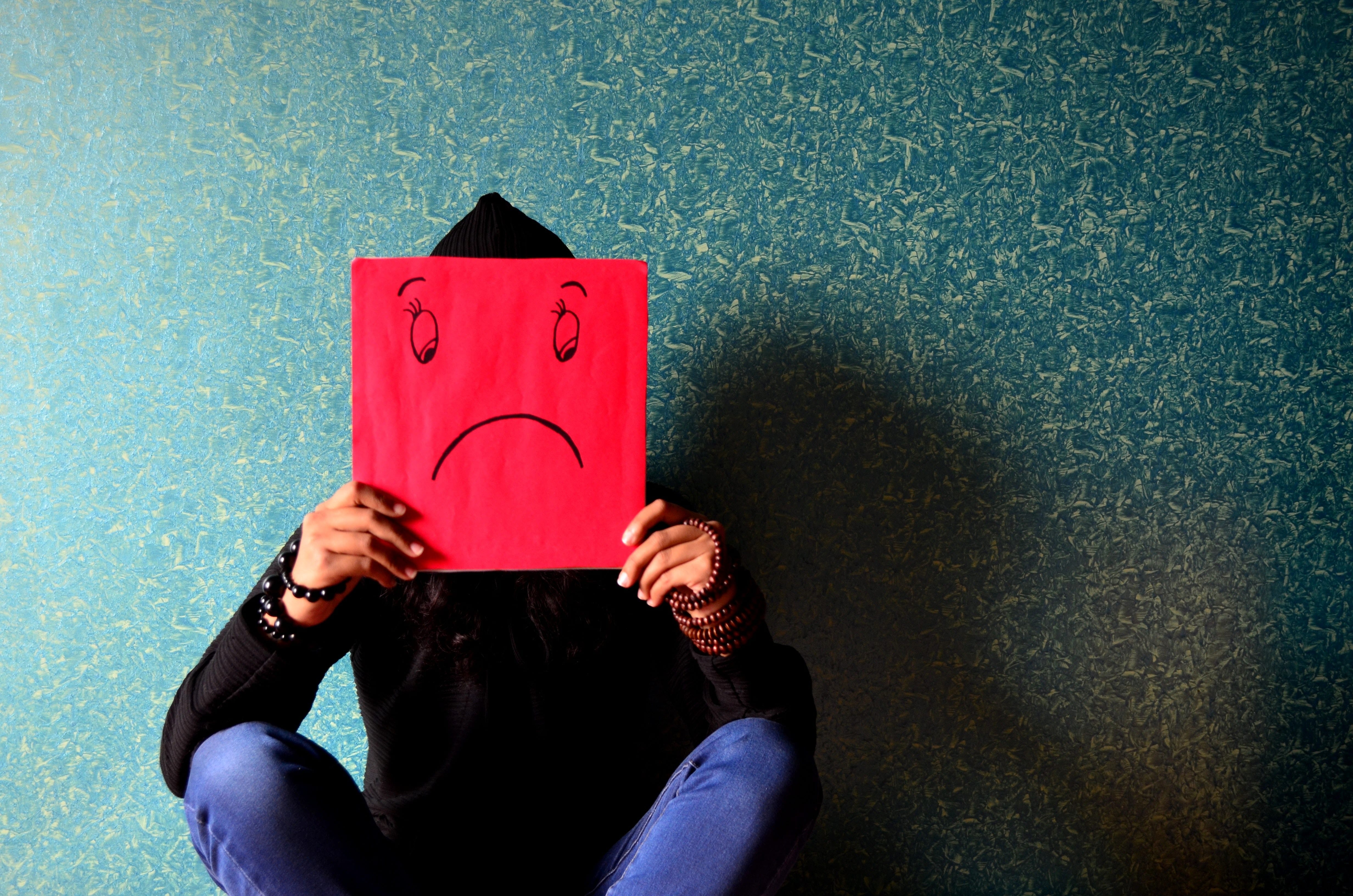 young adult sitting down in front of textured wall holding a red paper in front of face with a frown drawn on it