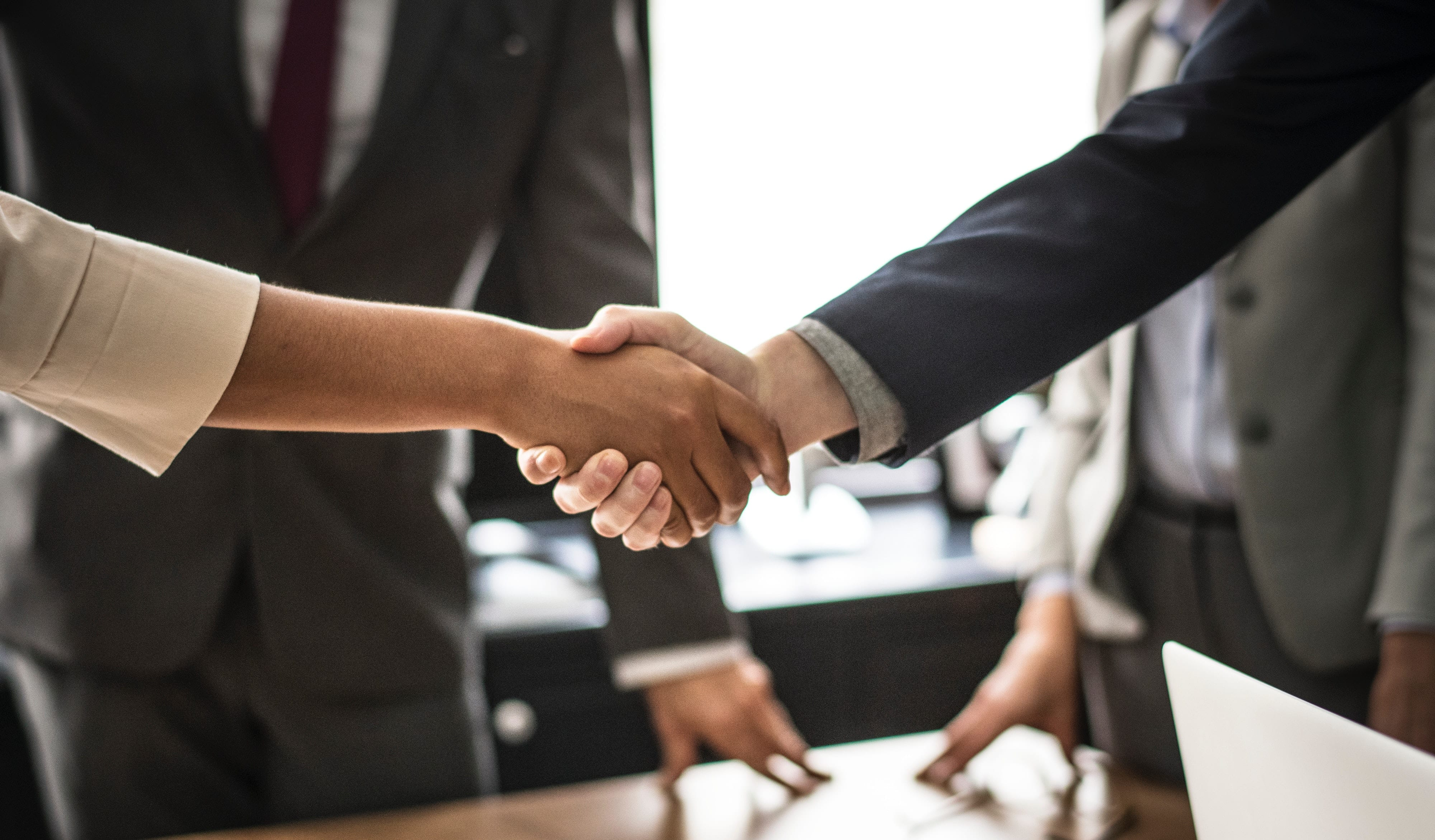 group of business professionals shaking hands while others wait in the background