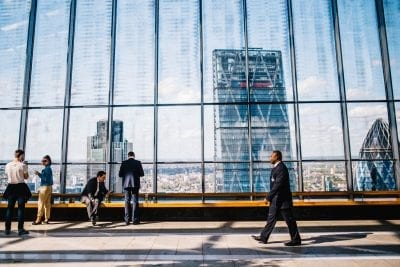 Business professionals taking breaks in a skyscraper with aerial views of London that has a bench