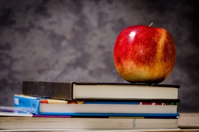 college text books with apple sitting on top