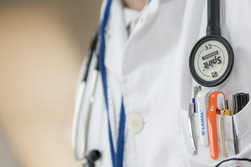 close up of a nurse's uniform with a stethoscope and pens in the pocket