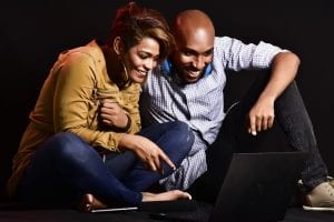 african man and woman sitting on floor watching tv show on laptop