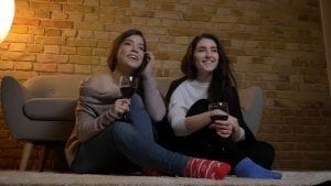 two young woman sitting on floor with wine watching favorite nurse tv show