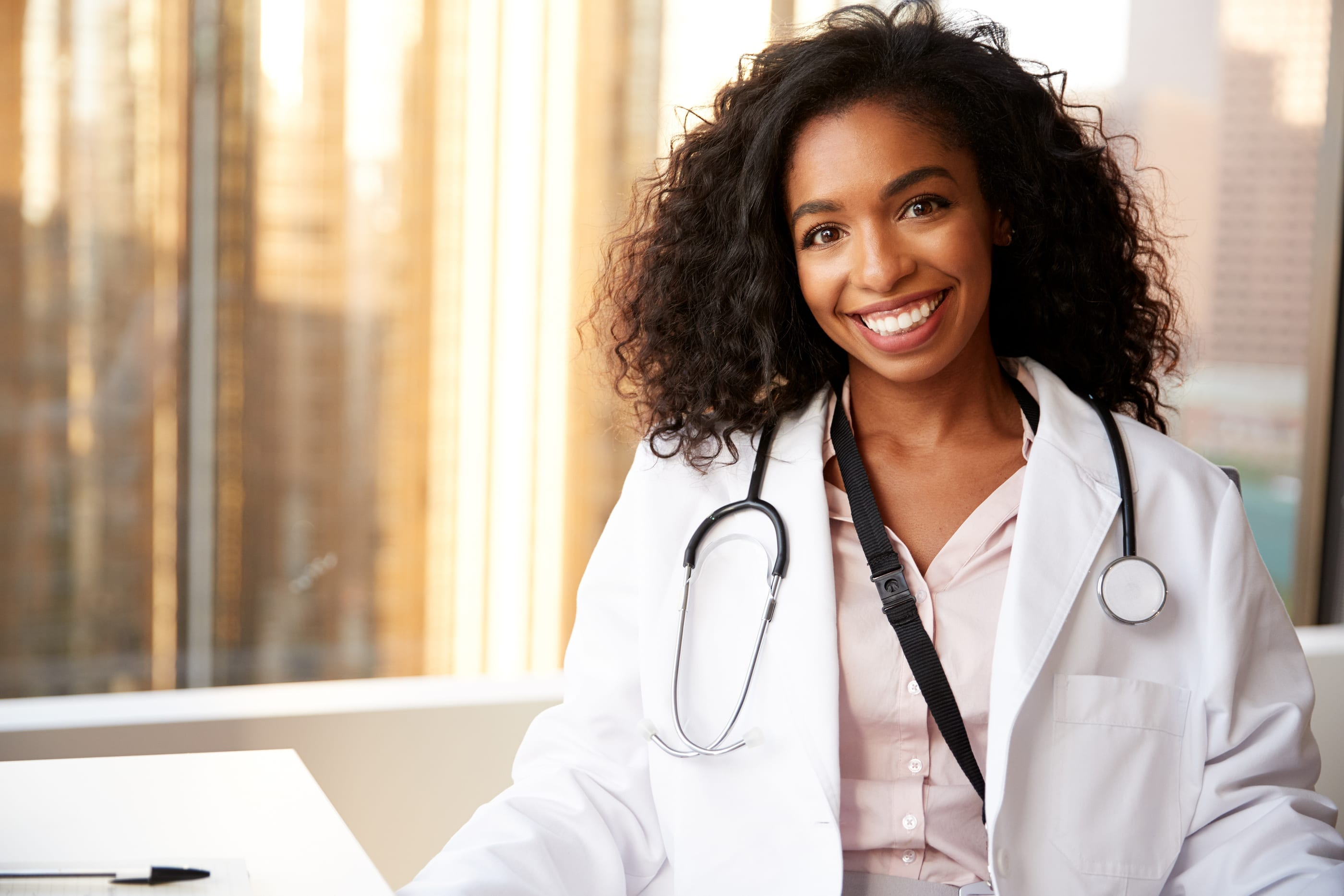 smiling african american oncoology nurse with city background