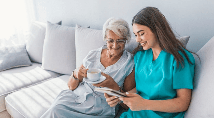 young woman on a nursing internship showing an elderly patient her notepad while she drinks tea