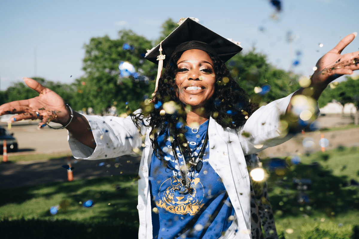 smiling african american nurse in cap and gown smiling and throwing confetti